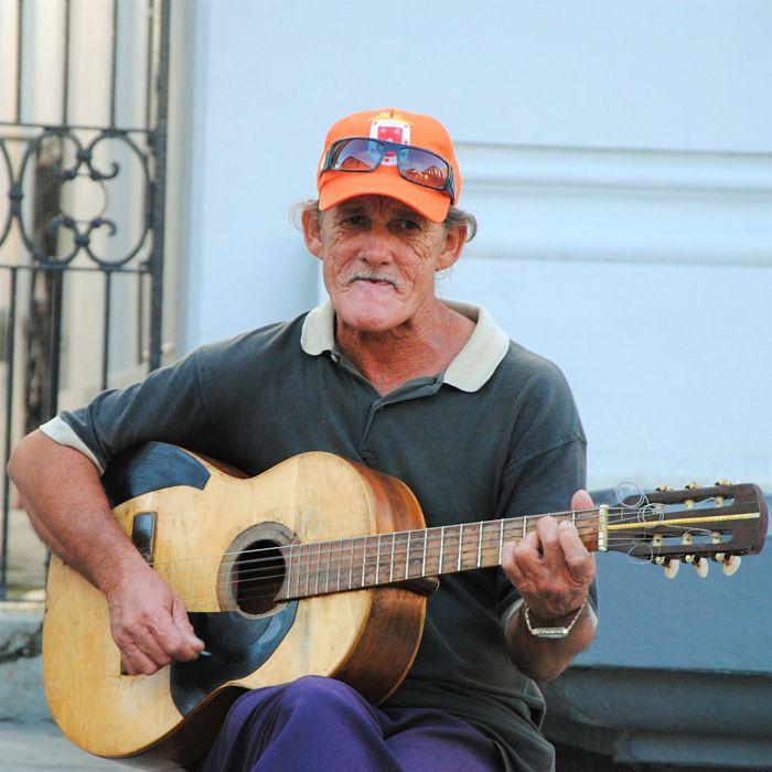 Un cubain joue de la guitare et siffle dans la rue