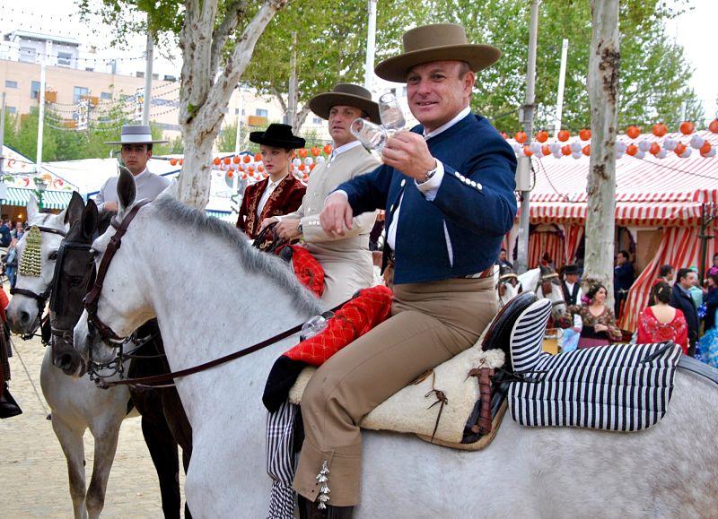 Sevillan attendant son rebujito sur le dos de son cheval à la Feria de Séville
